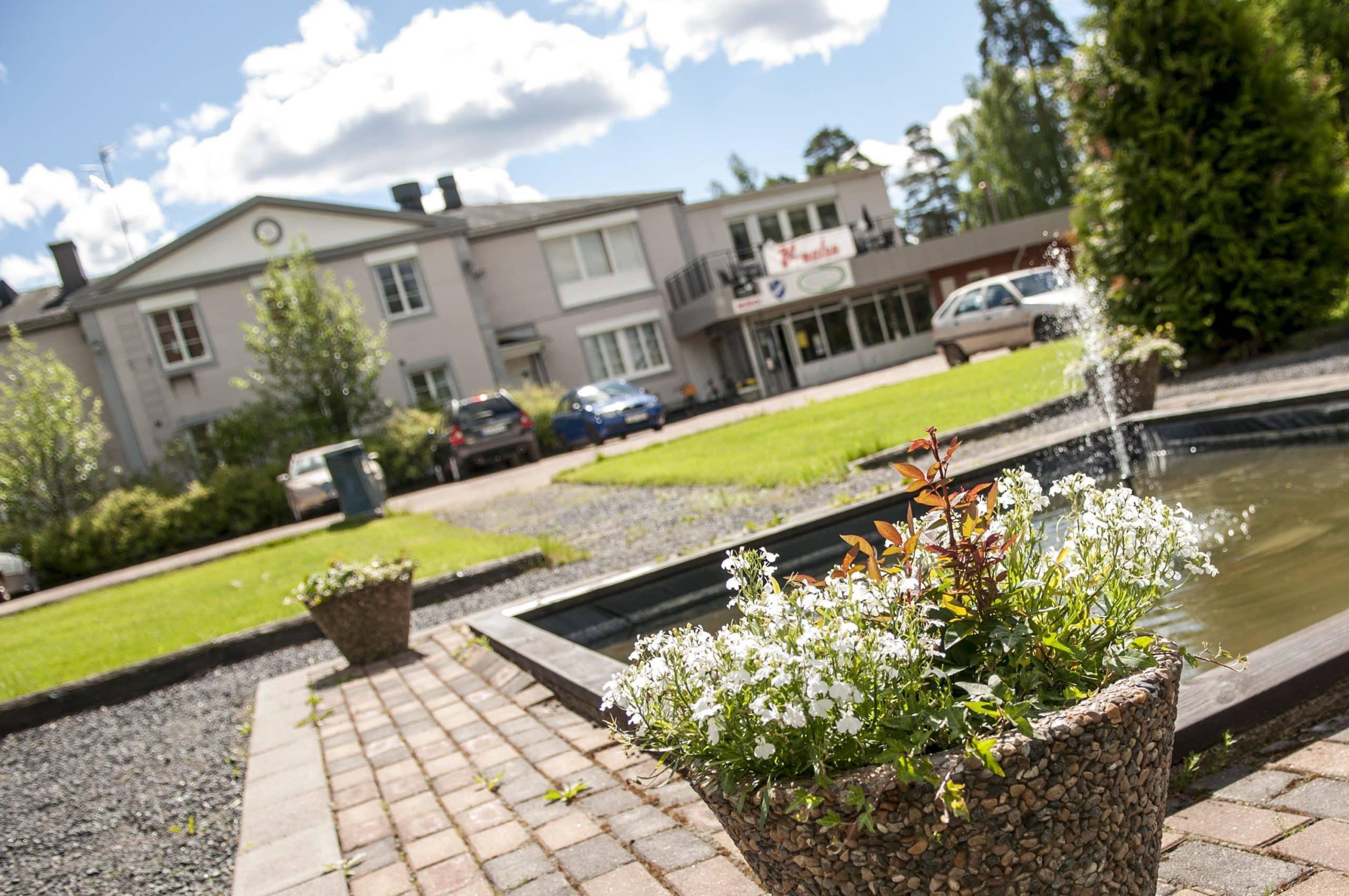 Munkfors Förenings- och konferenscenter i bakgrunden. I förgrunden syns en del av trädgården men blommor och en fontän.