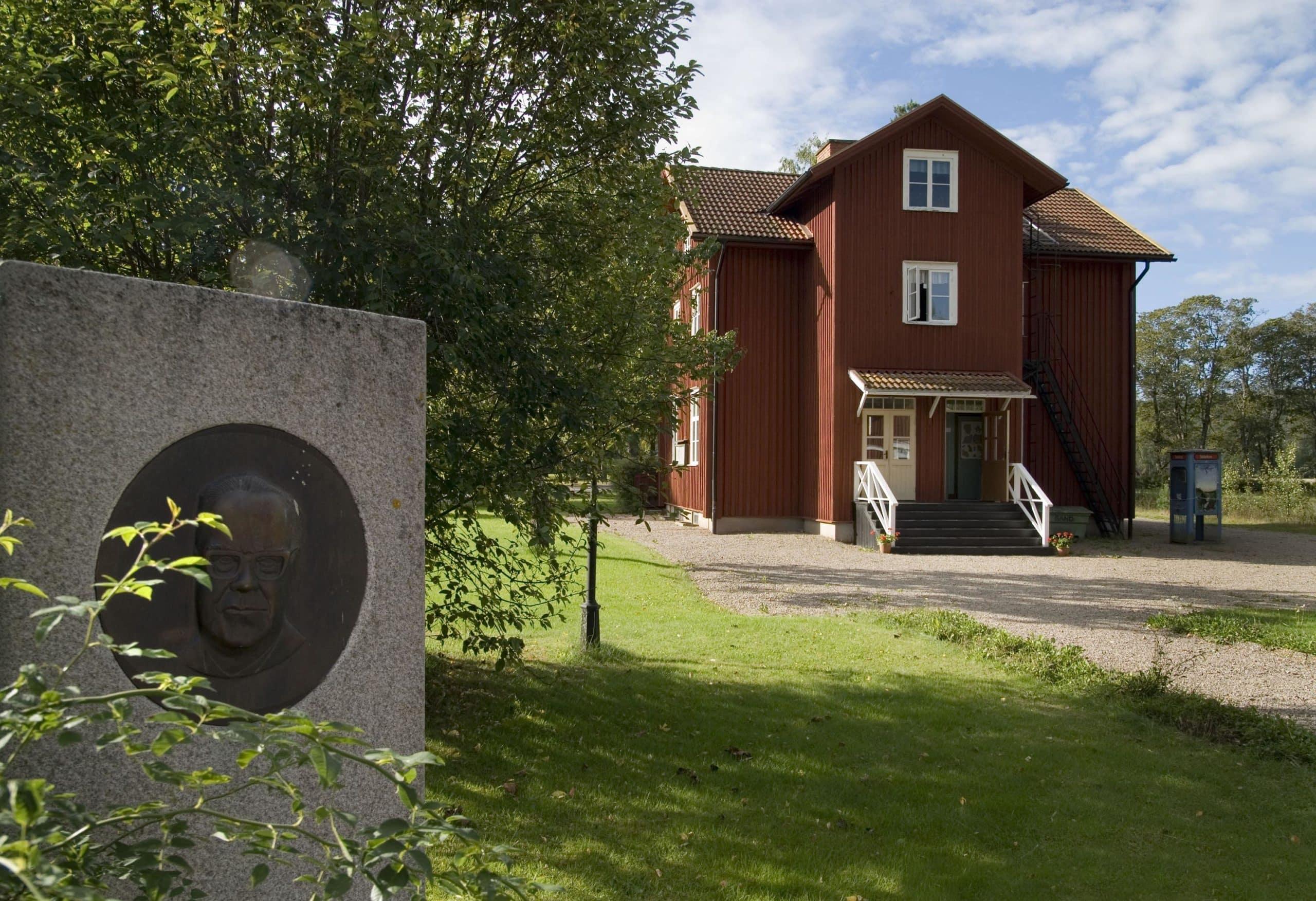 Erlandergården med dess röda fasad och i förgrunden en fyrkantig sten med en bild av Tage Erlander på.