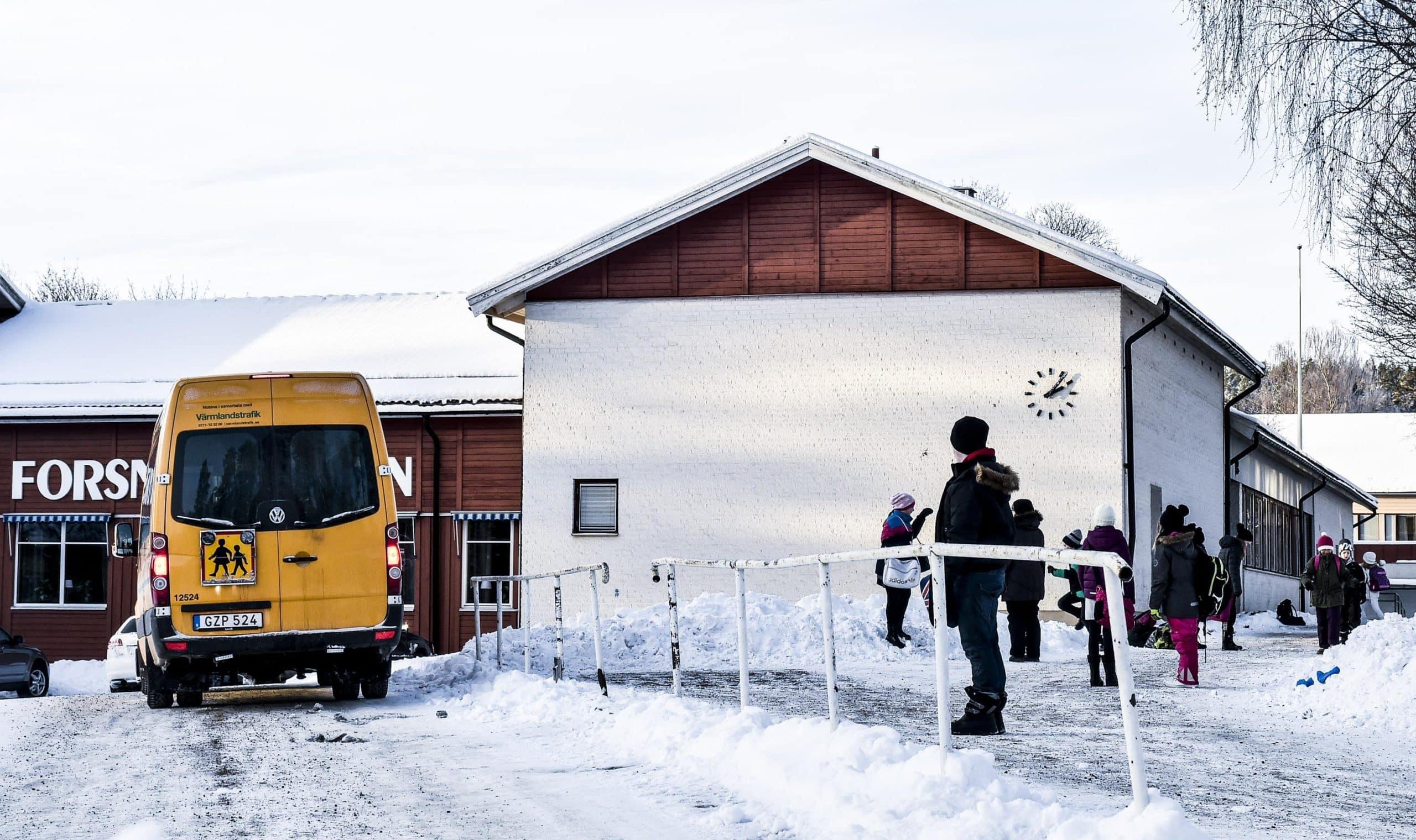 Nio elever i mörka vinterkläder väntar på skolskjuts utanför Forsnässkolan. En liten gul buss passerar framför barnen.