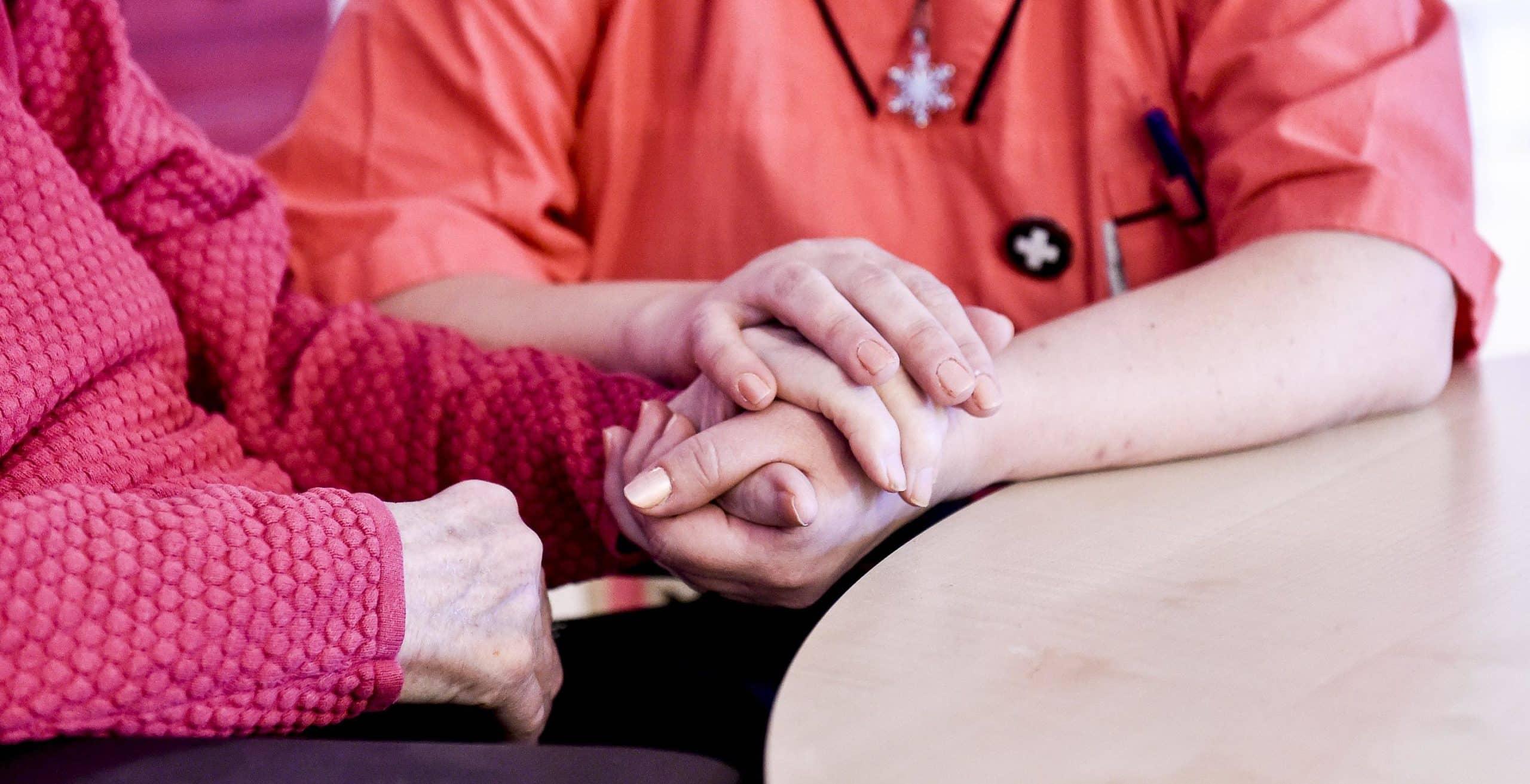 Två personer håller handen. En person är äldre och en person är yngre.