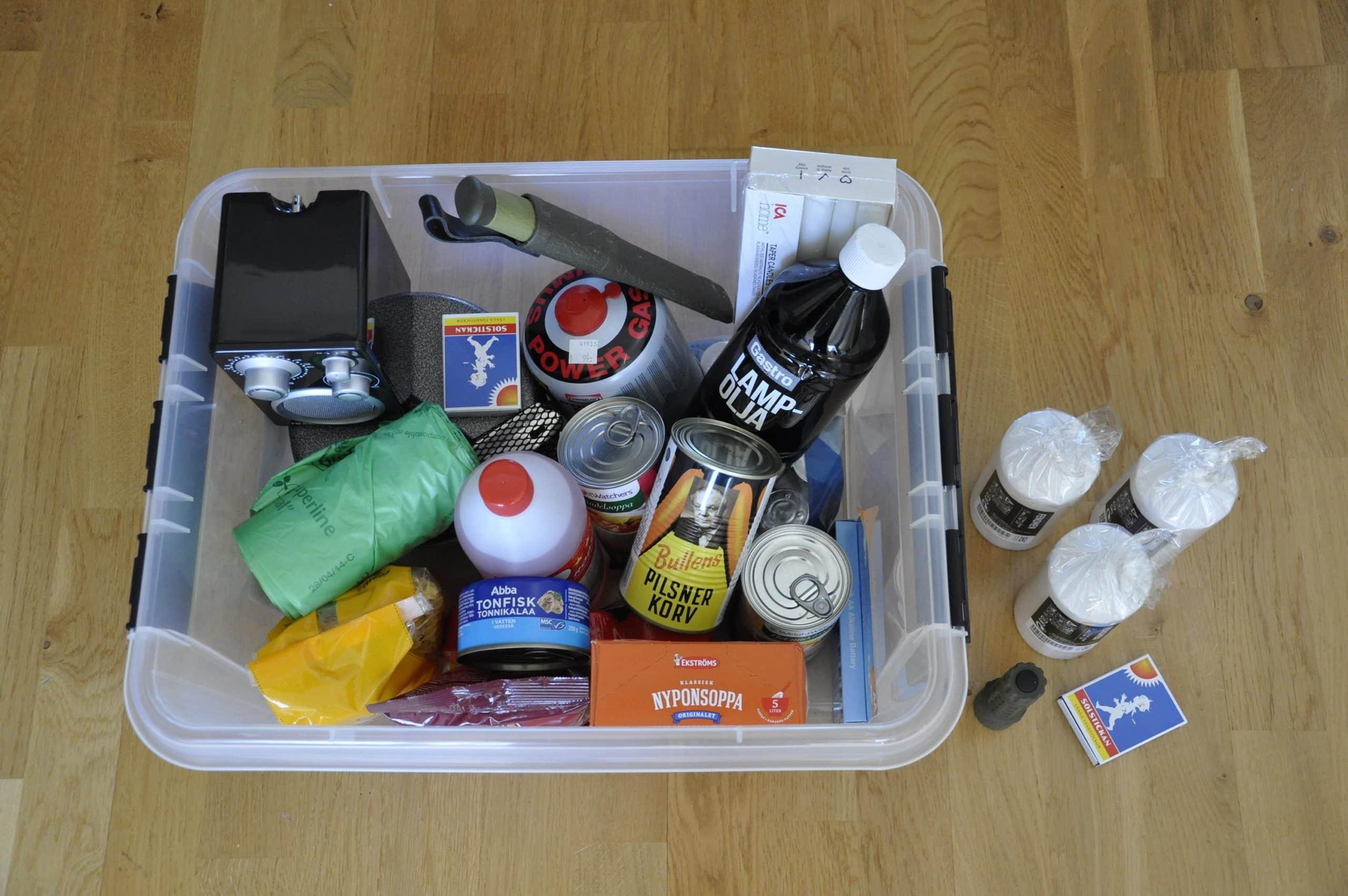 En plastlåda som innehåller saker som kan behövas för att klara krisen som konserver, värmeljus och tändstickor, plastpåsar, lampolja och gas för matlagning m.m.