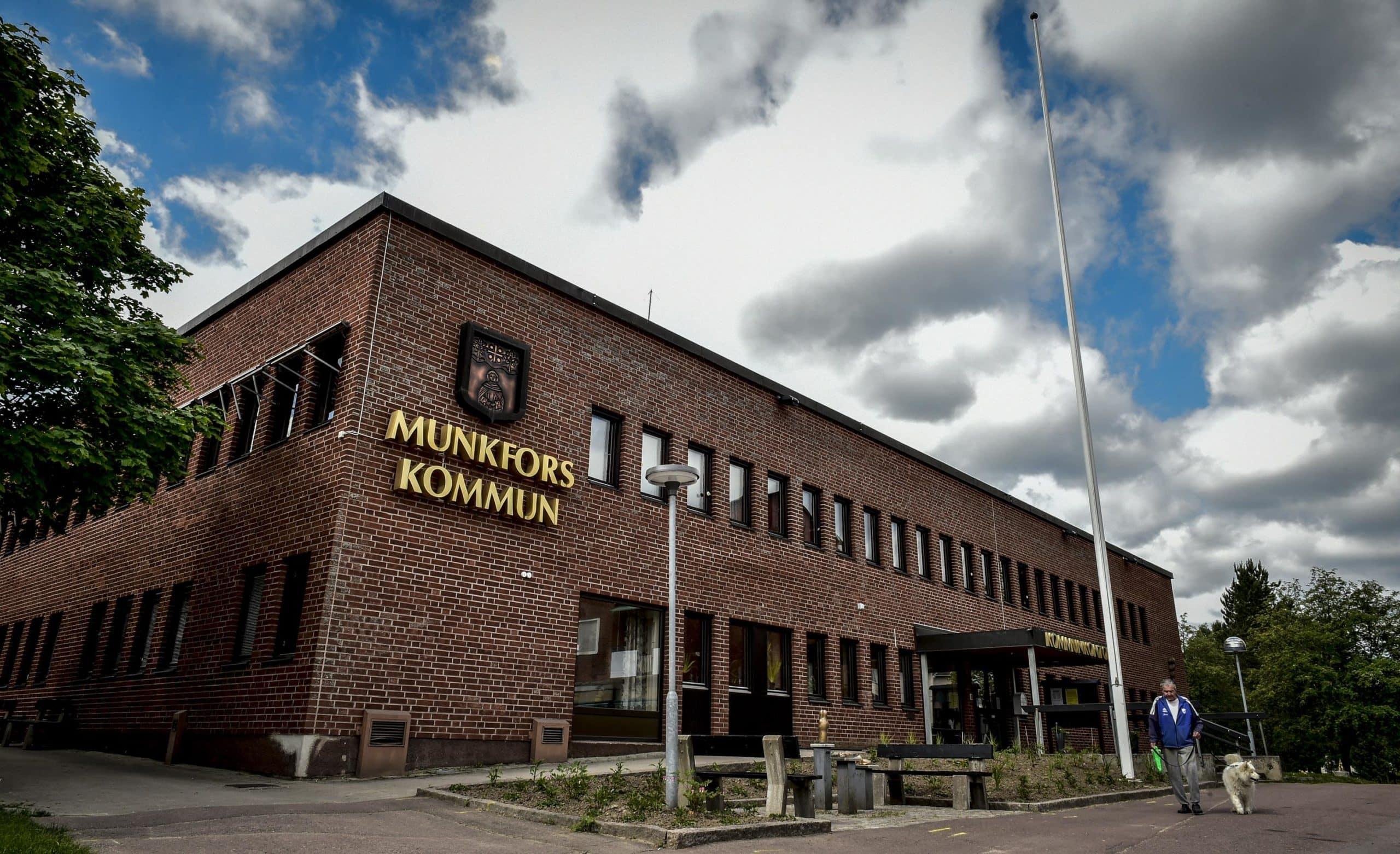 Kommunhusets framsida sett från marken och snett uppåt. På fasaden sitter en guldfärgad skylt med kommunvapnet och texten Munkfors kommun