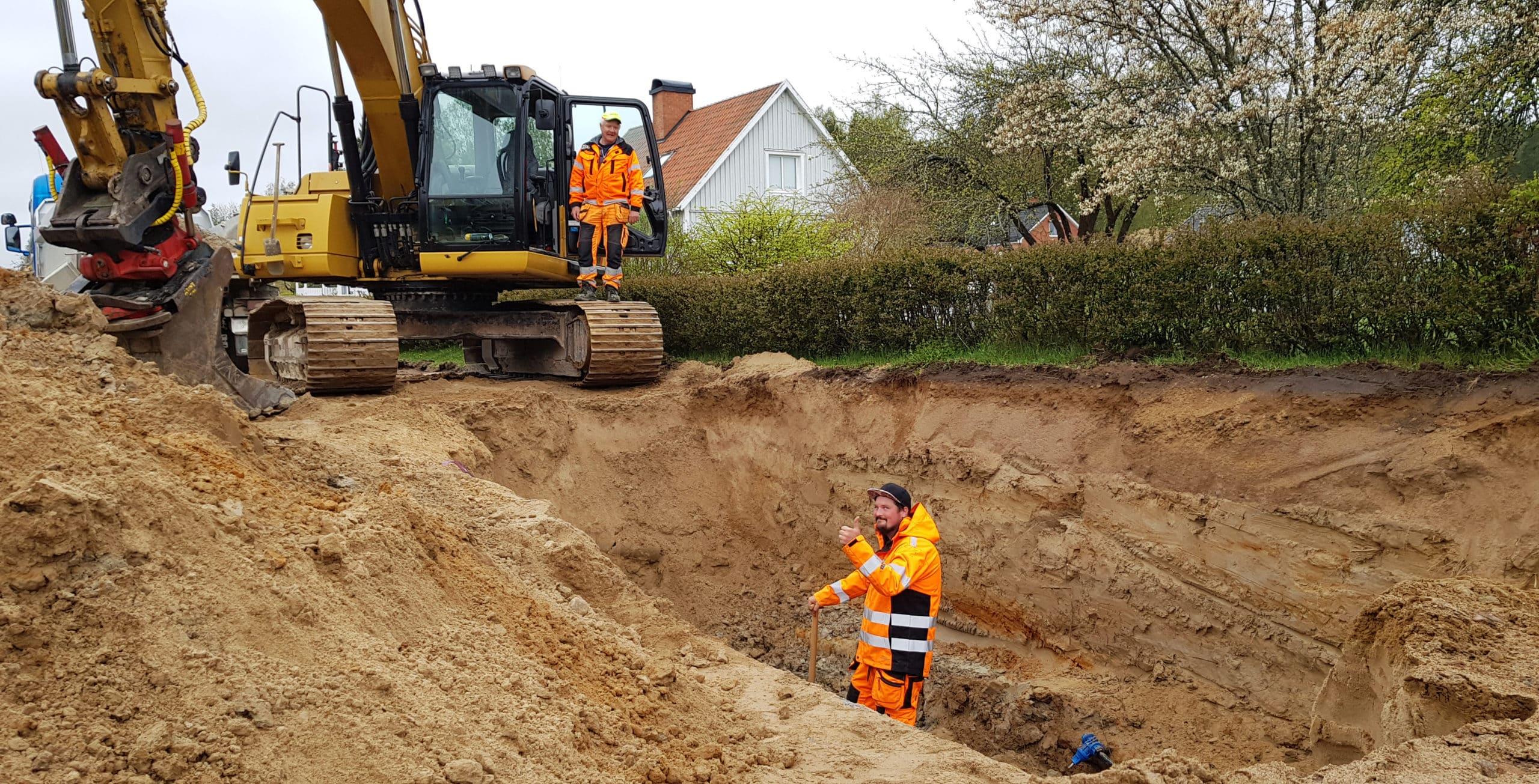 En arbetare i orange kläder gör tummen upp i en grop. En annan arbetare i likadana kläder står på en bandgrävares band vid gropens rand.