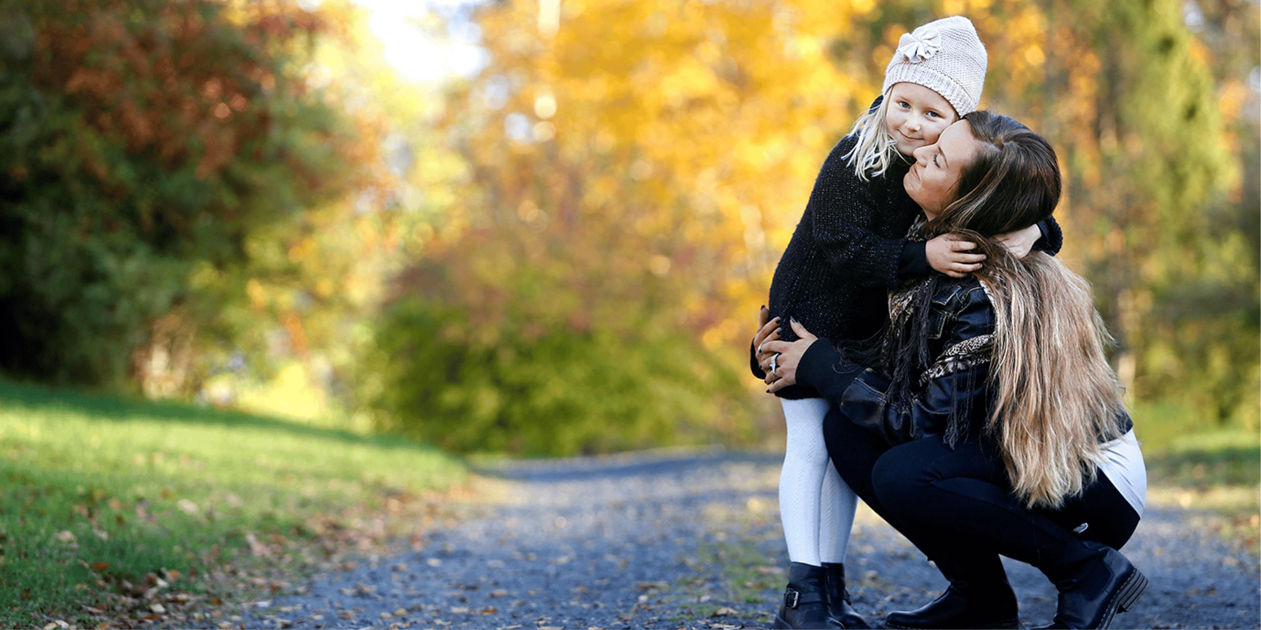 En vuxen kvinna och en flicka kramas på en grusväg. I bakgrunden finns träd med löv i olika färger.