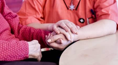 En medarbetare och vårdtagare sitter tillsammans vid ett bord och håller varandras händer.