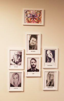 Svartvita bilder på Fjärilens medarbetare pryder en vit vägg.