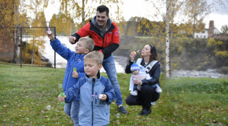 Mamma och pappa blåser såpbubblor tillsammans med sina tre barn vid Munkforsen.