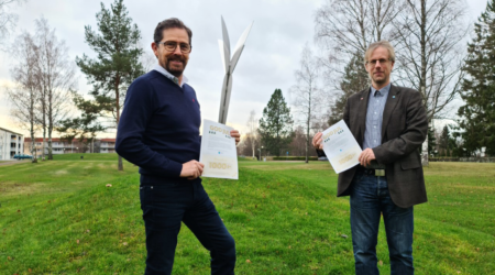 Kommunchef Jan-Olof Appel och kommunalråd Mathias Lindquist står utomhus vid en skulptur och håller i varsitt presentkort.
