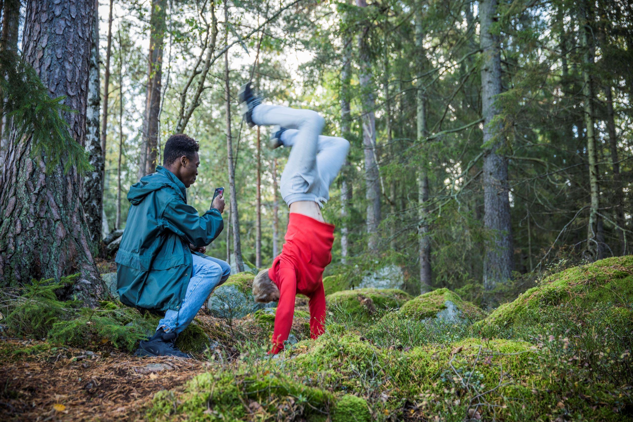 Kille fotograferar sin kompis som gör parcour i skogen.