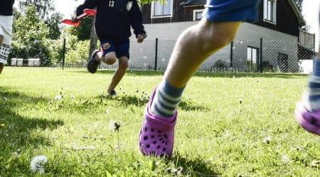 Barn som springer på en gräsmatta.